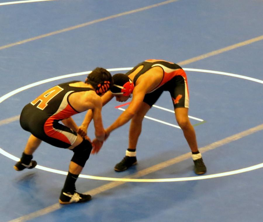 Two West wrestlers grapple in a match.