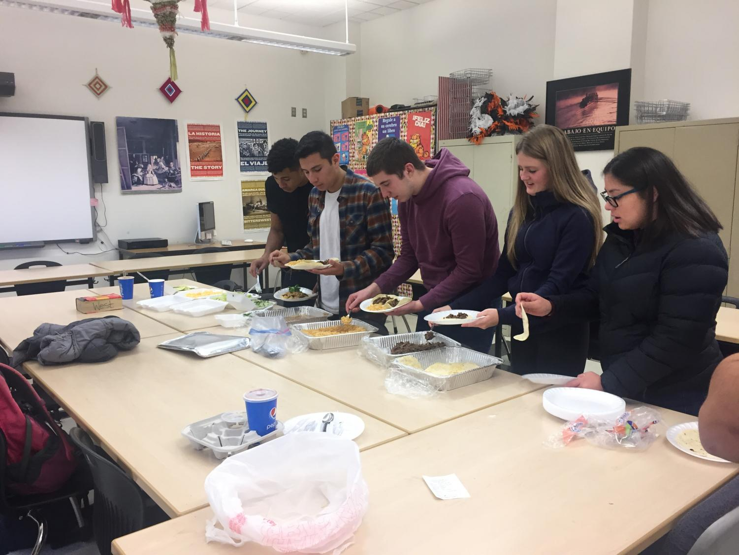 West students eating lunch at a potluck in a classroom.