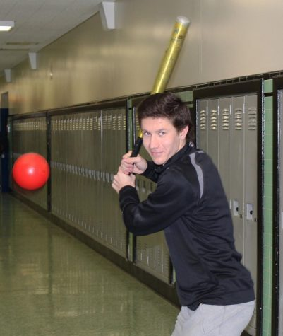 Jack Opinsky batting in the West Anchorage High hallway during class to show some of his summer activities.