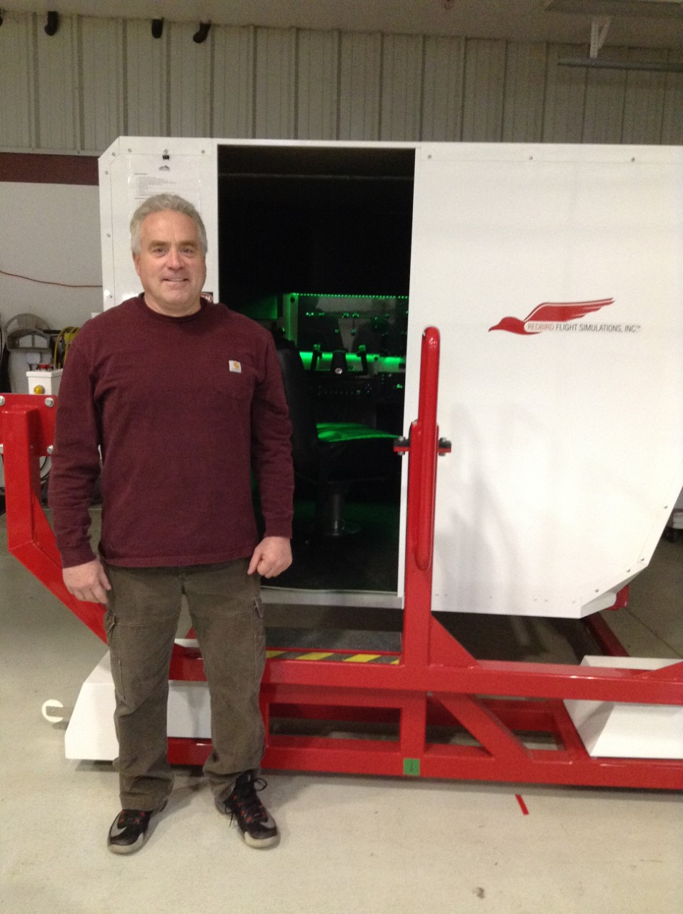 Al Merrill with his RedBird Flight Simulator that is used to teach and train rising pilots.
